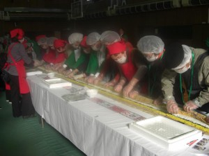 (2) They are rolling the sushi with bamboo-made wraps, slowly, carefully, and tightly.
