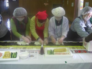 (1) Participants put some rice on seaweed which is on top of yellow steamed chrysanthemum petals. After that, they will put some cucumbers, egg, and other ingredients on the rice.